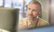 a male customer services representative on the phone to a customer