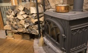 Wood burning stove with wool logs next to it