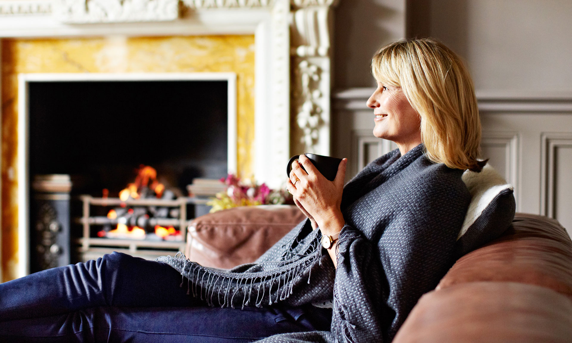 Woman sitting by the fire with a cup of tea