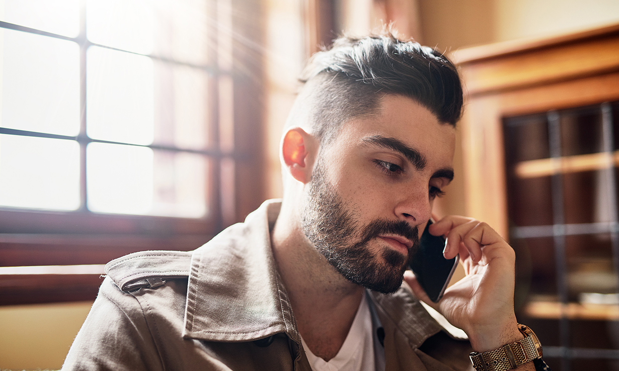 Shot of a handsome young man talking on a cellphone at home