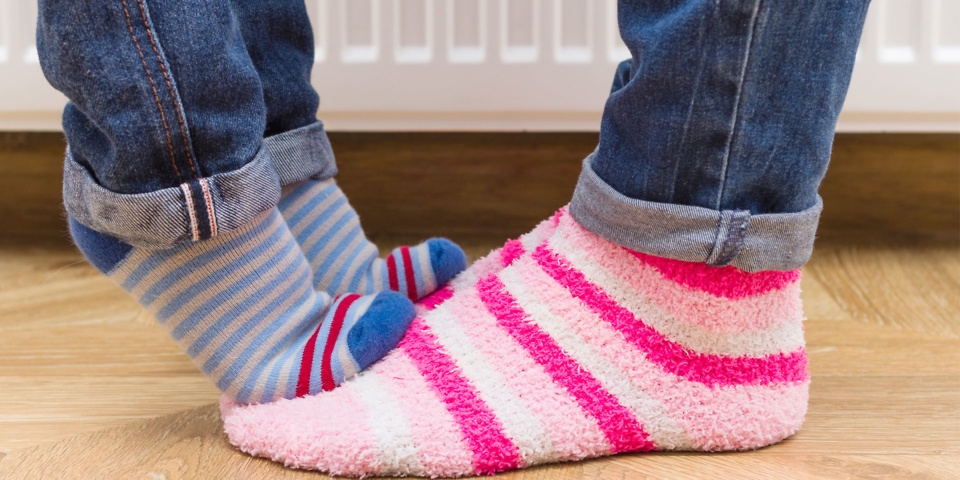 Child's feet standing on adult's feet in warm socks