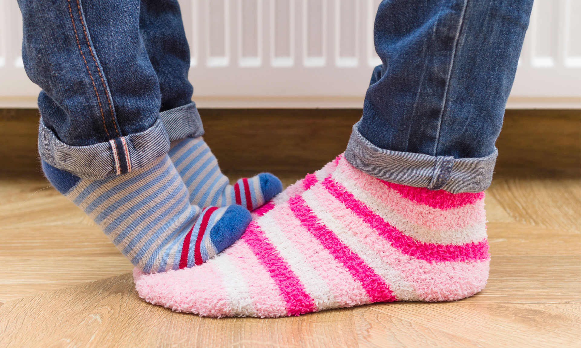 Child's feet standing on adult's feet in warm socks