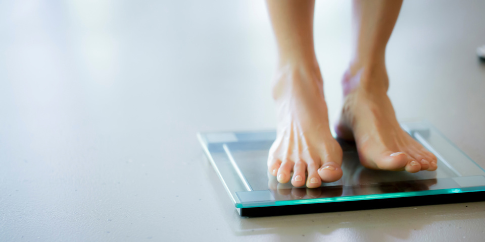 Woman standing on smart bathroom scales