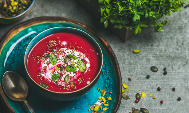 Red soup in teal coloured bowl with seed, cream and herb garnishing