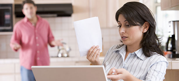 Woman with laptop in her kitchen looking disgrunted at an energy bill. Male partner in background, obviously disgrunted too.