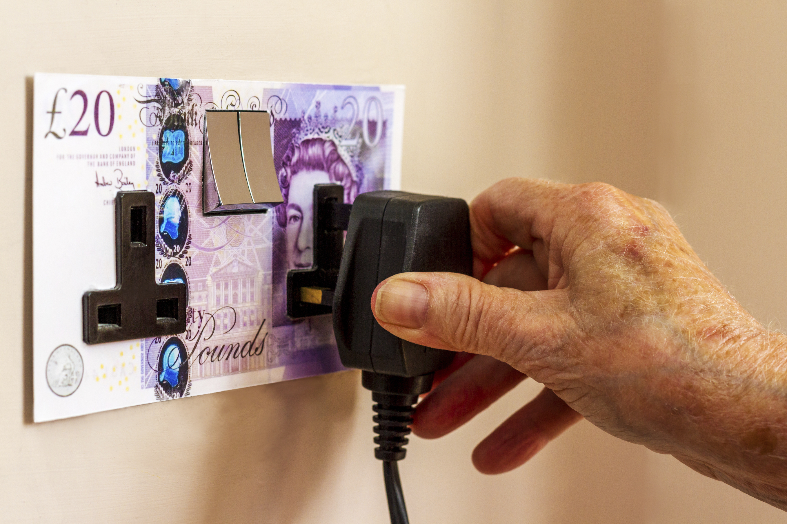 Plug socket with £20 notes on it- hand plugging in plug
