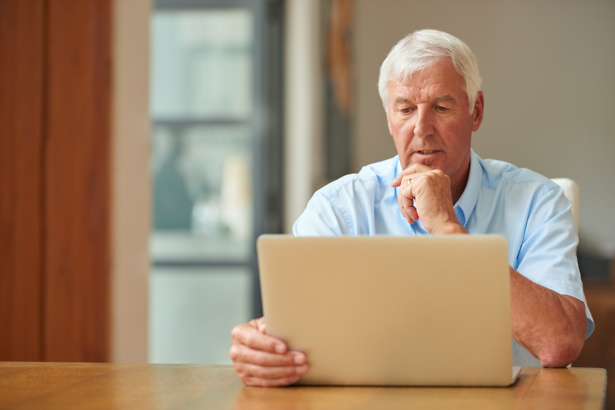 Senior man looking at laptop