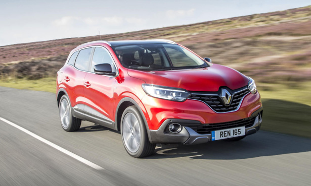 Red Renault Kadjar driving on a road in the moors