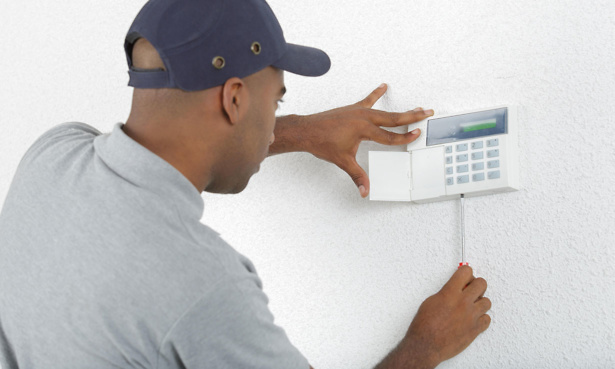 Installer fitting a burglar alarm