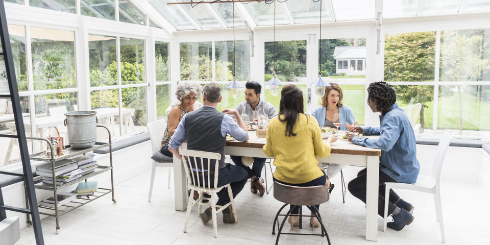 Six friends sitting around dinner table in naturally lit conservatory talking