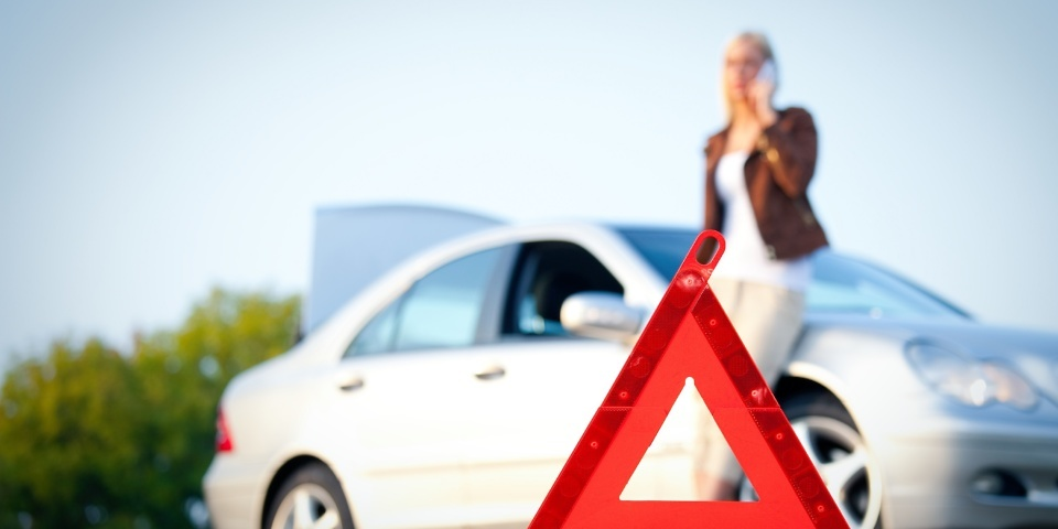 A young blonde woman with a silver car that broke down on the road. She has set up a warning triangle. She calls for help at a well-known automobile club with a mobile phone. She is waiting for the technician to arrive, while resting at her broke down car.