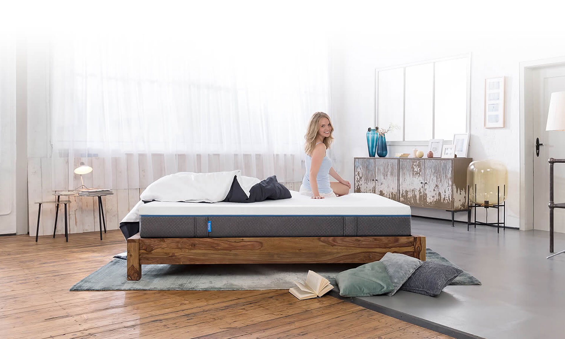 Lady sitting on Emma mattress bed in bedroom