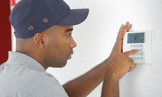 Man setting burglar alarm