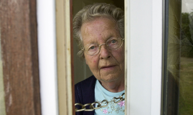 Elderly lady opening her door on the security chain