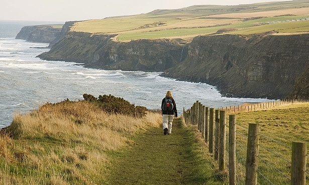 Picture of woman walking along a cliff edge path on the Cleveland Way with a view of the sea