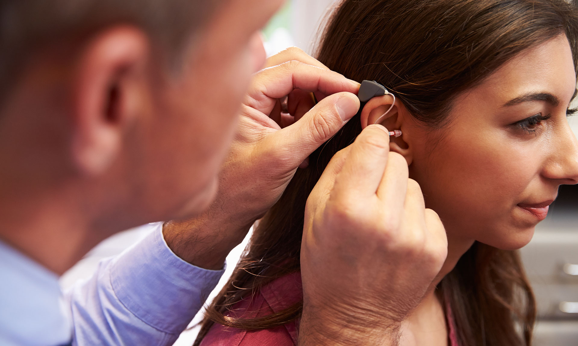 Man fitting a woman's hearing aid