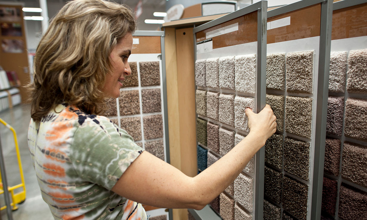Woman looking at carpet samples in a showroom