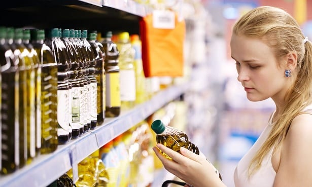 Woman buying olive oil from supermarket shelf