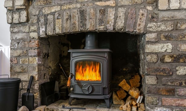 Lit small wood-burning stove in a brick fireplace