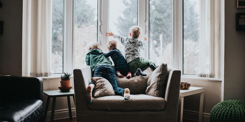 Three kids looking out of double glazed windows