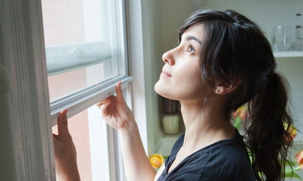 Woman opening a double glazed sash window