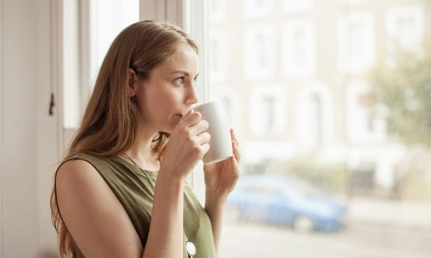 Young woman drinking a cup of tea looking out of a double glazed window