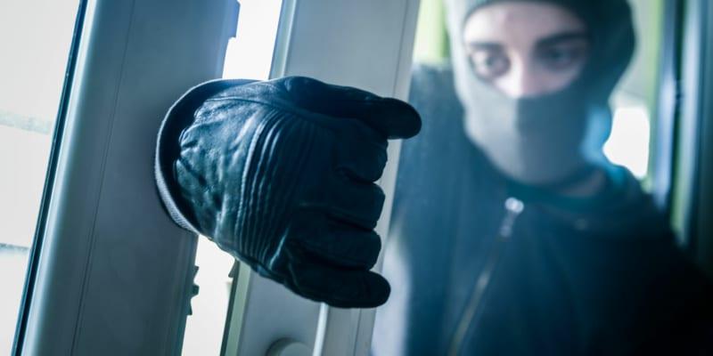 Burglar breaking into a house through a window