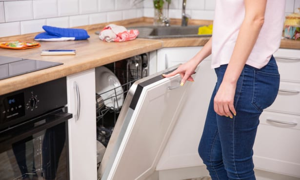 Woman selecting program from integrated dishwasher control panel