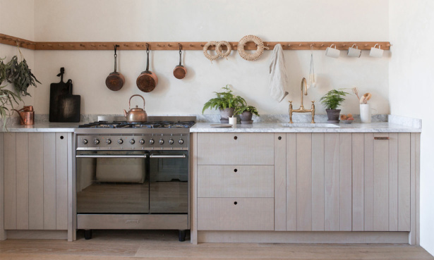 Shaker style wooden kitchen cabinets and hanging hooks and marble worktops
