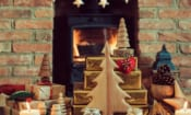 Christmas presents stacked in front of a wood-burning stove