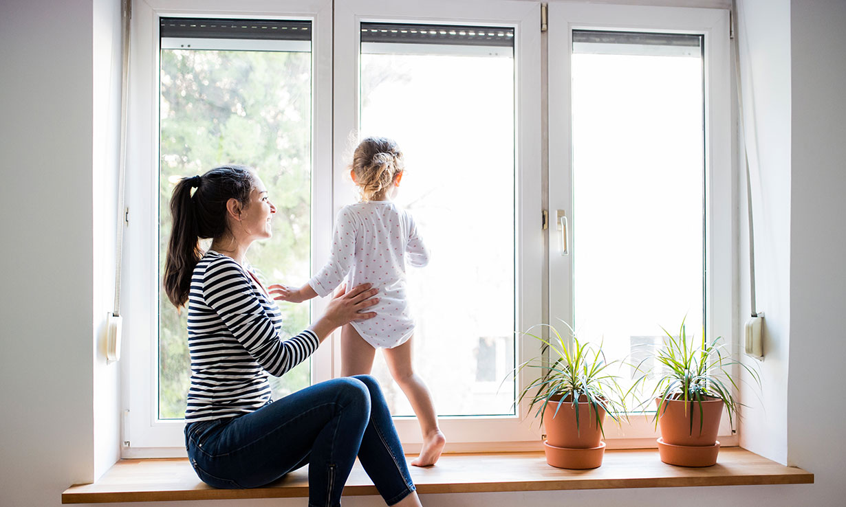 A woman and child in front of double glazed windows on a sunny day