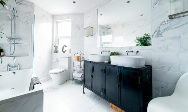White marble bathroom with freestanding bath and black storage unit