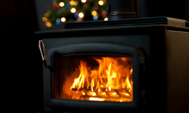 Wood-burning stove with Christmas tree lights in the background