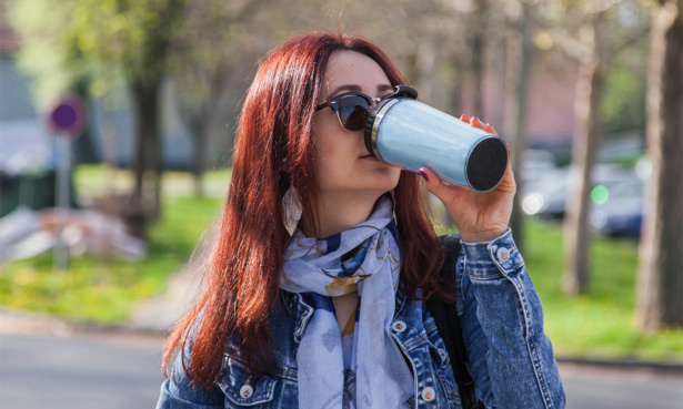 Woman drinking from a travel mug on the go