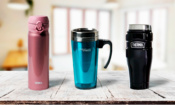 Three Thermos travel mugs lined up on a table