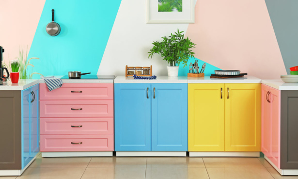 Colourful kithen with blue, yellow and pink cupboards and walls