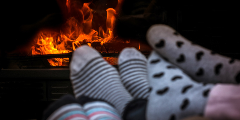 Three pairs of feet in socks in front of a wood-burning stove