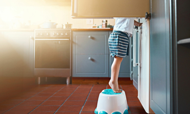 child on a footstool reaching into a fridge freezer