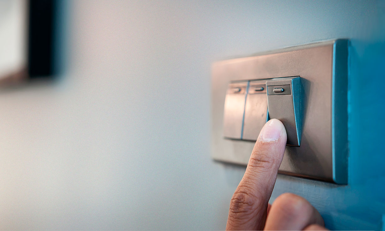 Finger pressing a light switch to turn the electricity on