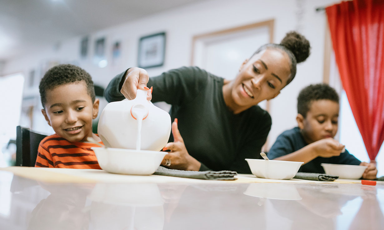 Mother pouring milk into cereal bowls