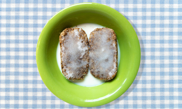 Two weetabix sprinkled with sugar in a milk in a green bowl on a blue and white checkered tablecloth