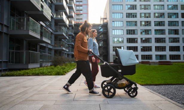 Couple pushing Bugaboo Fox2 with flats in the background