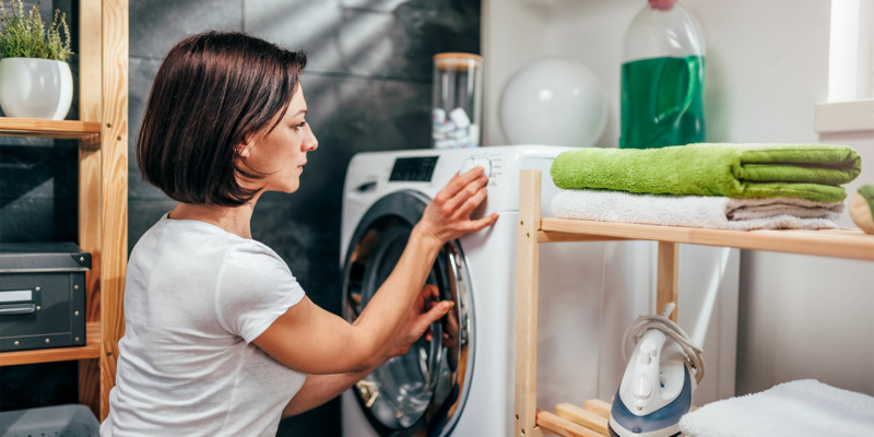 Woman in a utility room setting her washing machine program