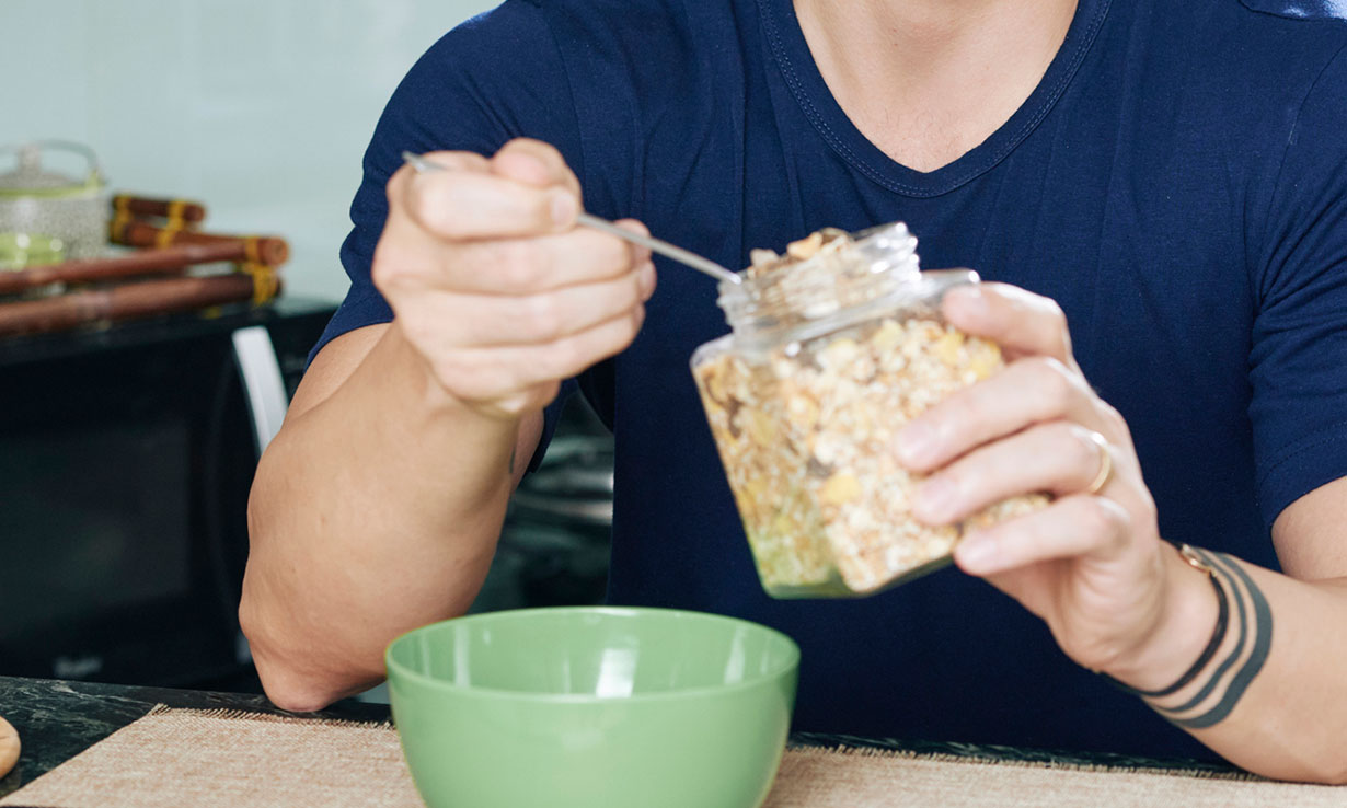 Man spooning muesli into a bowl from a jar
