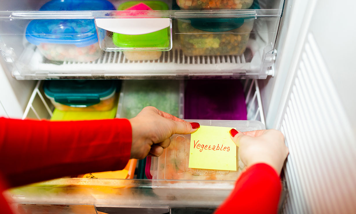 Plastic container of vegetables being labelled with sticky note