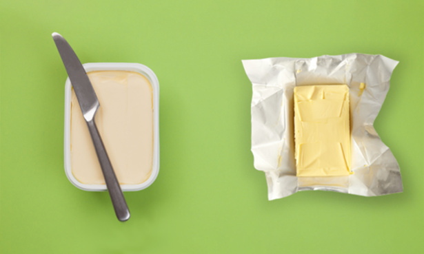 Tub of spreadable butter and an open packet of butter side by side