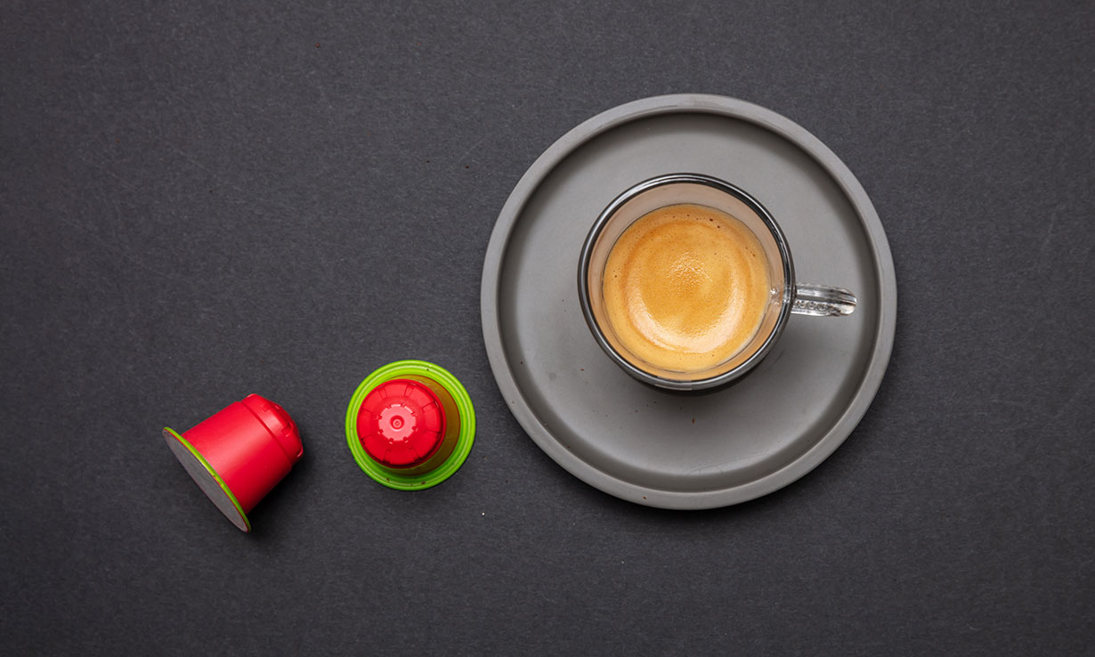 Cup of espresso on plate next to compatible coffee pods