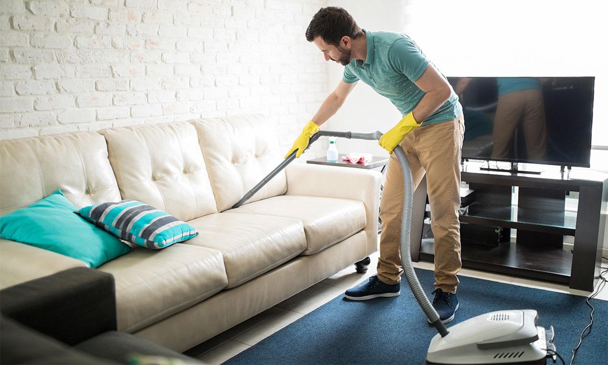 Man vacuuming a white sofa
