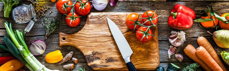 Fruit and vegetables around a chopping board
