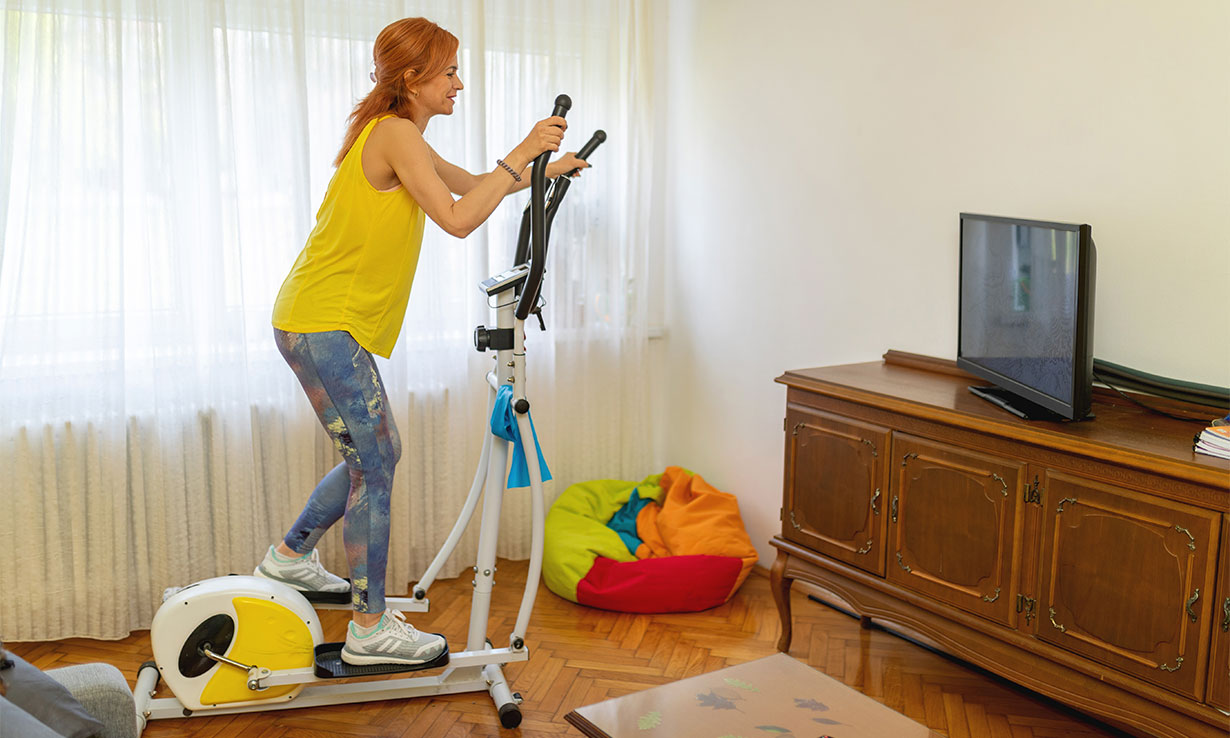 woman using cross trainer at home